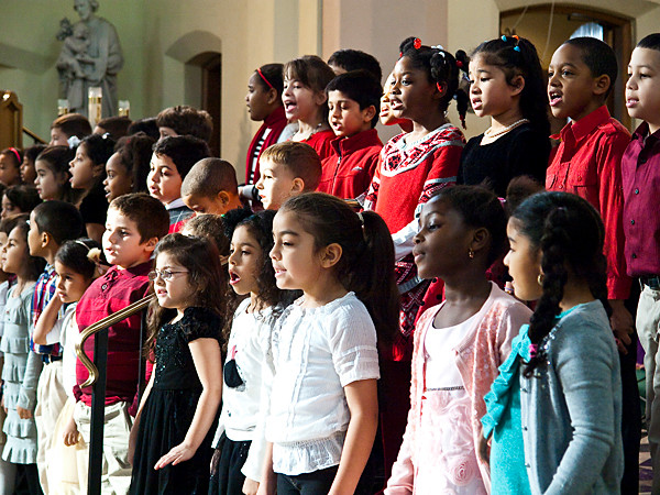 Kindergarteners, first graders and second graders, sing 'Extraordinary Merry Christmas' during the school's Christmas show at St. John's Church on Dec. 21.