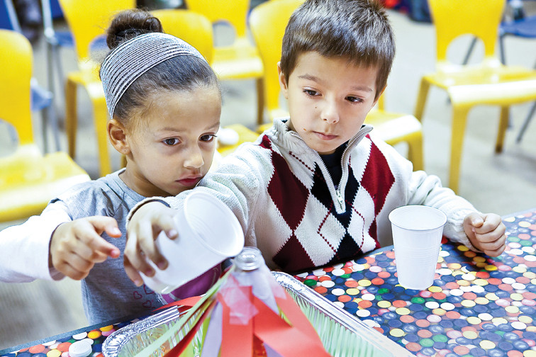Jeanette Rodriguez, 4, and Luke Leshaj, 6, pour warm water into a model volcano made of plastic bottles and paper as part of the Fun Science at Riverdale after-school class at the Riverdale Library on Jan. 4.