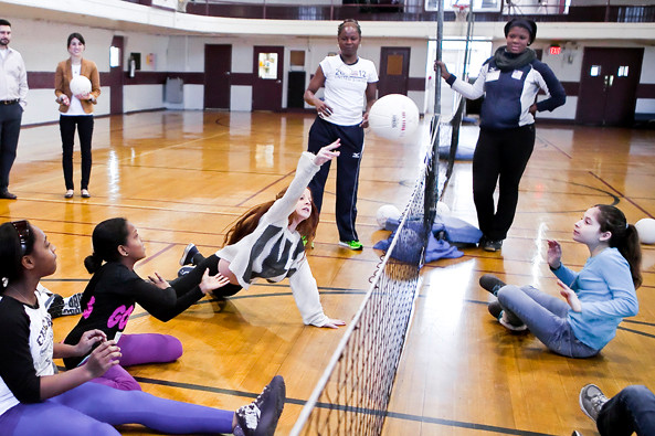 Paralympian Volleyball players Kari Miller and Nicky Nieves, standing at the net, teach sitting volleyball to students at Horace Mann on Jan. 10.