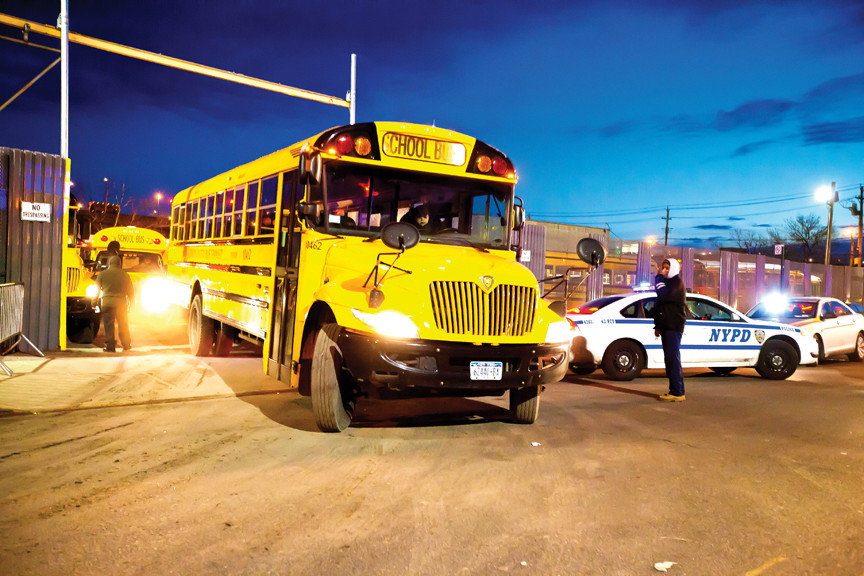 NYPD officers monitor a Castle Hill bus yard as Consolidated Bus Transit vehicles drive off near strikers on Jan. 18.