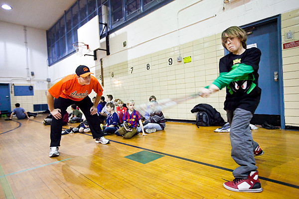 James Corey, 9, takes a few swings for South Riverdale Little League coach Alex Patasalos at the David A. Stein Riverdale/Kingsbridge Academy, MS/HS 141 gym on Saturday.