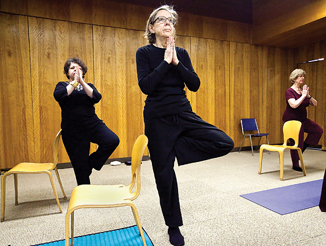 Dagmaris Cabezas, Nancy Karg, and Alicia Villafane stand in tree pose during the Riverdale Library's Gentle Yoga class on Feb. 8.