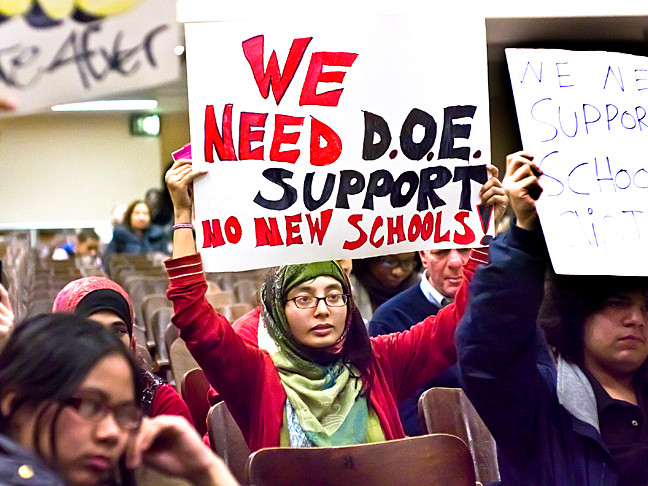High School Senior Fatima Uddim, 17, holds up a sign at a Feb. 21 public hearing to protest the Department of Education's proposal to co-locate two new schools inside DeWitt Clinton.