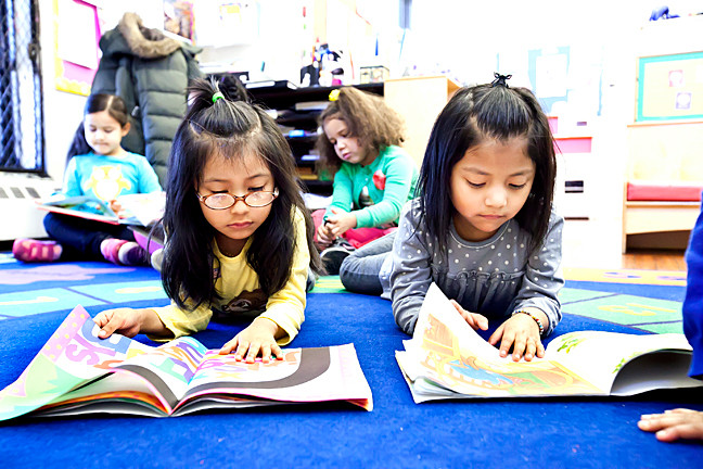 Denise Millan, 4, and Angelyn Dominguez, 5, read on the rug at Kingsbridge Heights Community Center on March 4.
