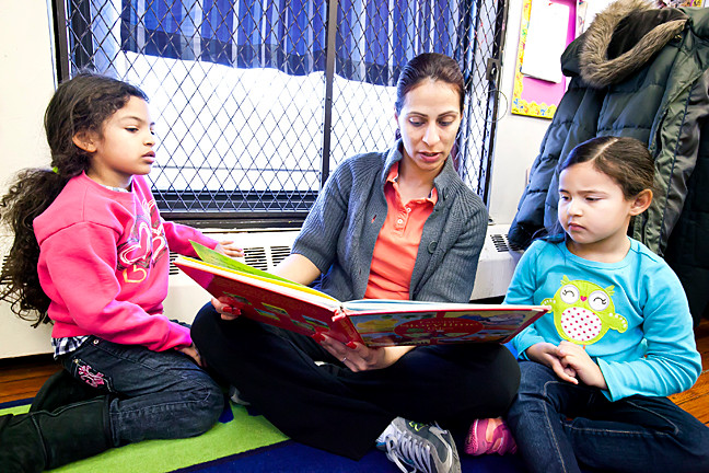 Penelope Acevedo and Abby Belliard, both 4, listen to teacher Iris Polanco at the Kingsbridge Heights Community Center on March 4.