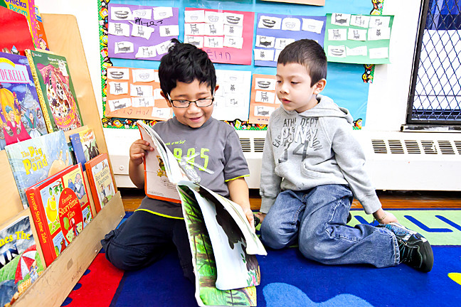 Jose Flores and Luis Aleman-Surrano, both 5, share a book.