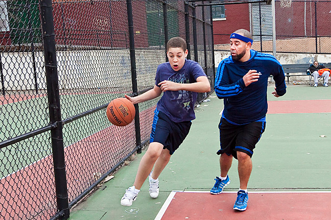 Frank Mejia, Jr., 13, goes head to head with his father Frank Mejia Sr., during a basketball game at the Spuyten Duyvil Playground basketball courts on March 28.