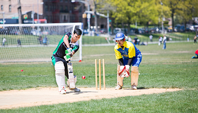 Priyang Choudri, batter for the New York Juggernauts defends while Ajith Bhaskar Shetty prepares for the arrival of the ball during a cricket game at the Parade Ground Opener at Van Cortlandt Park on Sunday.
