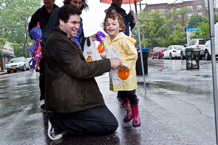 Steve Grossman holds his daughter, Lilly, 3, as she dances under the cover of a tent at the Riverdale Spring Festival on Sunday.