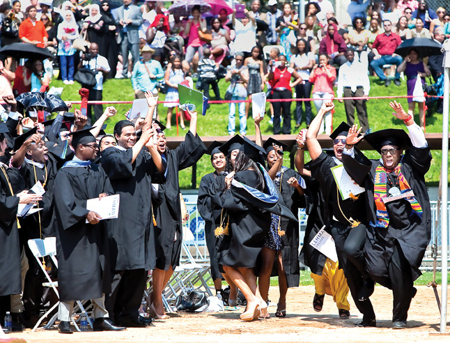 Journalism, Communications and Theater graduates stand up with excitement at the Lehman College graduation on May 30.