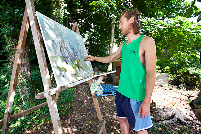 Riverdalian Ian Kirby, a painter, works on his piece 'Compostosaurus' on Independence Avenue on June 21. Mr. Kirby said his piece was inspired by composting and how it can transform an environment.