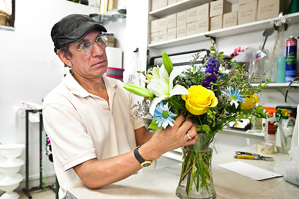 Winston Soriano puts the finishing touches on a flower arrangement at Flowers by Zenda at 5217 Broadway on Monday.