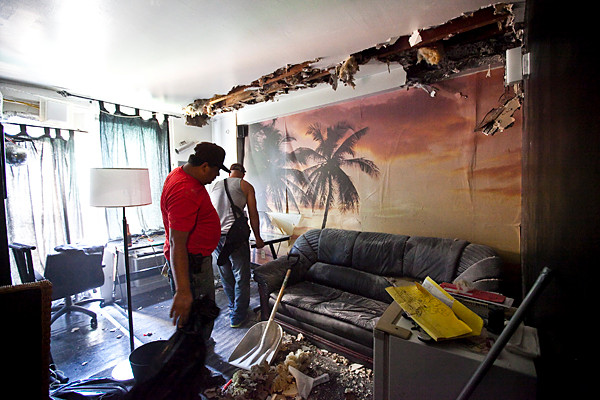 All City All City Restoration workers clean up debris in Victor Marrero's apartment on June 10, a day after a fire broke out in 3840 Orloff Ave.