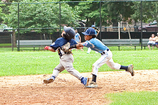 Miguel Batista, 10, a first baseman for Kingsbridge Little League, reaches for the ball for an out against Forest Hill at Marcus Garvey Park in Harlem on Saturday. Kingsbridge went on to win 10-9 in the District 23 championship.