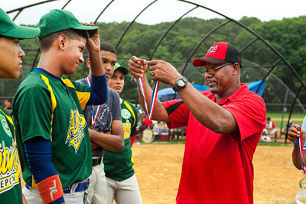 Johnny, President of Van Cortlandt Baseball League, gives out participation medals to Wilmer Soriano, 14,