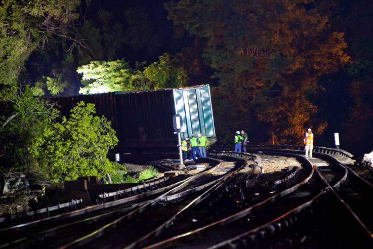 Shortly after midnight, railroad workers survey the scene of a garbage train derailment near the Marble Hill station.
