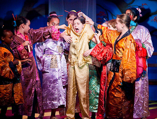 Leila Haller, 11, as Mulan, reacts to dressmakers, matchmakers and close relatives as they try to make her prim and proper for suitors.
