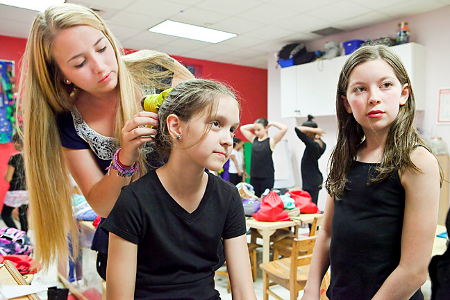 Jessica Lavery,19, works on Sarah Baum, 10, putting every hair in place in the dressing room.