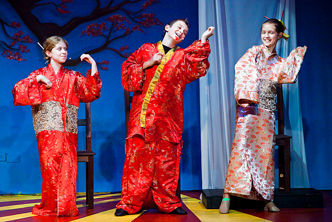 Olivia Santo, as Zhang, Josh Goldin-McCarthy as Mushu, and Sarah Baum as Yun, celebrate Mushu�s success.