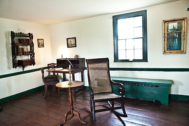 The rocking chair and the wall mirror, at top right, were original possessions of Edgar Allan Poe. Today they�re in the parlor of Poe Cottage.