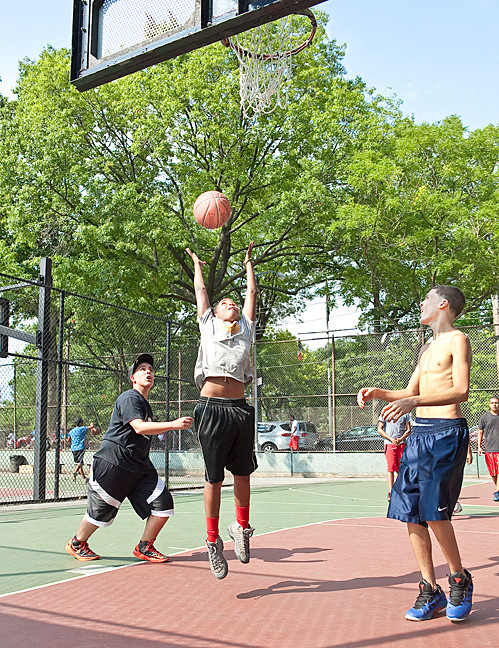 Rifat Hadbbeth, 14, Jose Pantoja, 11, and Kenneth Espinal, 15, above, shoot some hoops at Bailey Playground on Aug. 11.