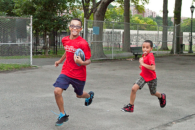 Robert Castillo, Jr., 14, and Brian Carmona, 9, play touch football at Van Cortlandt Park on Aug. 11.