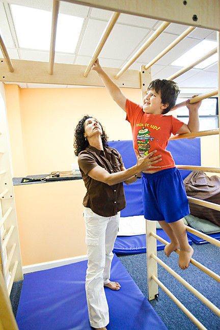 Moriel Hirsch-Hoffman, 5, swings across the monkey bars as therapist Dorian Pascoe, of Pascoe Pediatric Physical Therapy, provides guidance on Aug. 16.