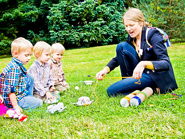 Children who made turtles out of paper bowls during a family arts project at Wave Hill on Saturday watch as Lise Murdock organizes a parade of paper pets.