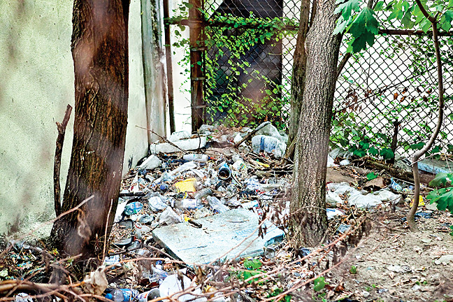 At the entrance to the John F. Kennedy Campus, located at 99 Terrace View Ave., it's easy to add litter to a growing pile of trash, but a chain link fence makes clean up hard.