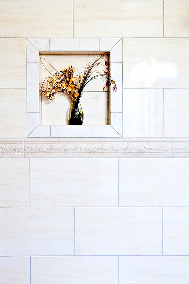 A decorative tile abounds in a tub enclosure. Above the bas relief belt line, a niche for a bouquet of dried flowers is carefully defined with a cut tile picture frame border.