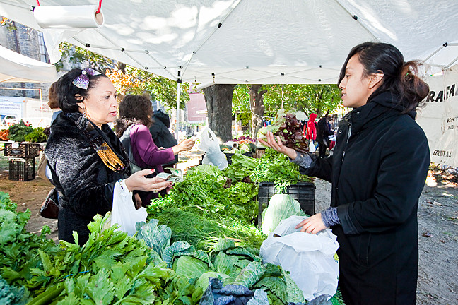 Mercedez Polanco purchases recao, which she incorporates in traditional Latin foods, and other greens from Consuelo Hernandez, a co-organizer of the market. Ms. Polanco said the recao costs ten times as much at supermarkets.