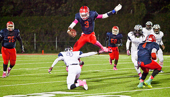 JFK's Anthony Cruz, No. 3, leaps in the air and avoids Canarsie's Brandon Hollingsworth, No. 4, at the JFK homecoming game on Oct. 25.