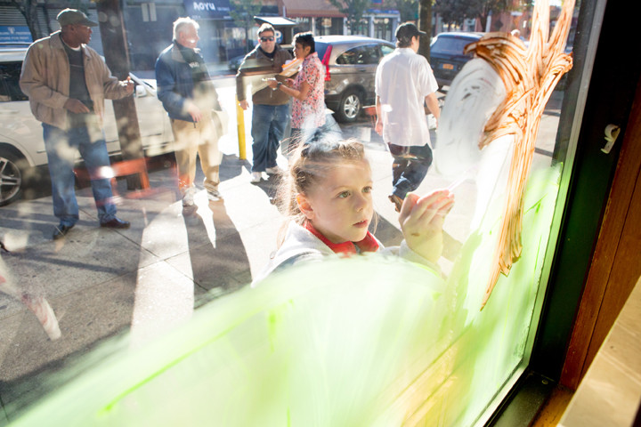 Avannah McManus, 8, paints a Blue Bay Restaurant window during the 57th annual Halloween window painting contest sponsored by the Kiwanis Club of Riverdale on Saturday.