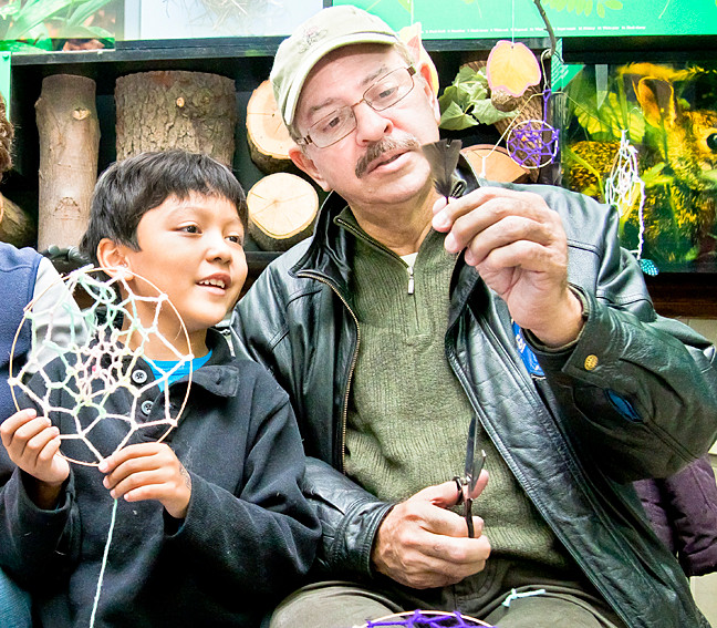 Jesus Cofresi shows his grandson, Joshua Cofresi, 6, how to trim a feather as the two take on the delicate task of fashioning dreamcatchers at a Native American crafts event at the Van Cortlandt Park Nature Center on Sunday.
