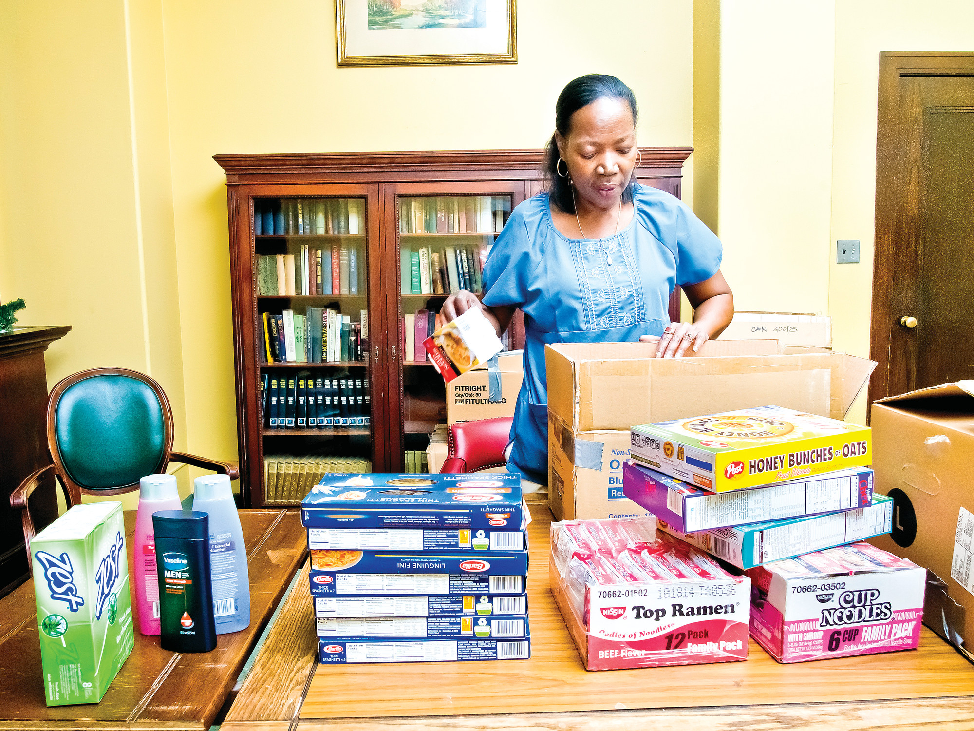 Cornelia Thompson sorts food donations for victims of Typhoon Haiyan into boxes at the Methodist Home for Nursing and Rehabilitation on Monday.
