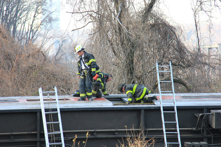Firefighters climb up onto overturned train cars to rescue riders trapped inside.