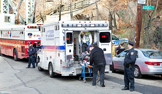 First responders place injured passengers into an ambulance on Edsall Avenue.