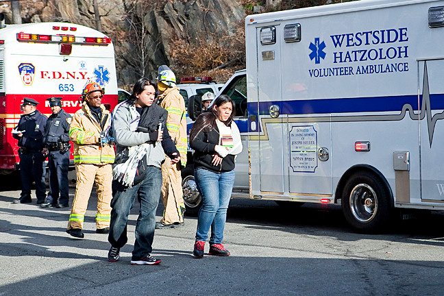 Survivors of the MTA Metro North derailment walk towards an ambulance on Edsall Avenue.