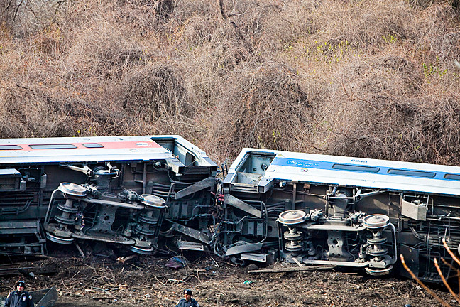 Two Metro North train cars lay on their sides after derailment.
