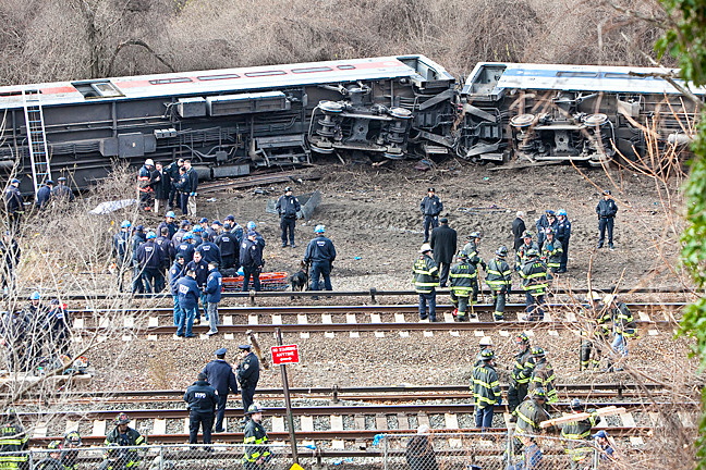 Officials at the scene oversee the recovery and begin an investigation of the derailment.