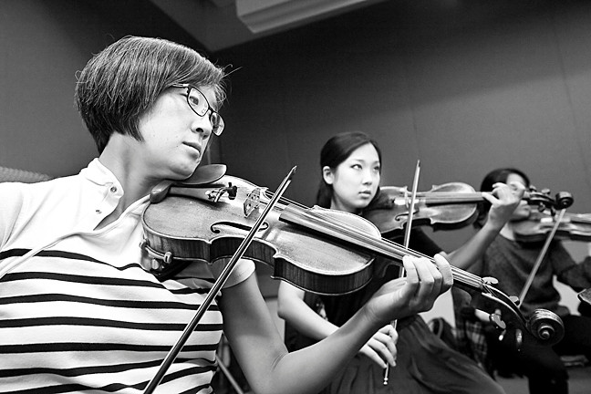 Violinists Salley Koo and Grace Park rehearse.