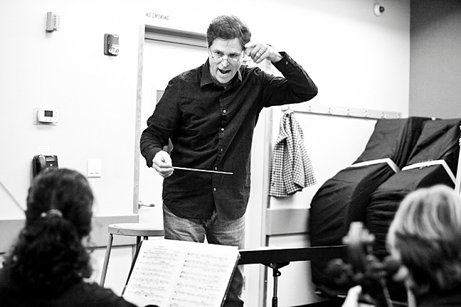 Conductor Mark Mandarano guides musicians in an October rehearsal.