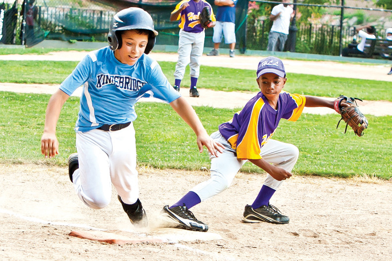 Brandon Fernandez, of the Kingsbridge Little League, pushes for a tough out at first base against Harlem Little League at Inwood Hill Park on July 8. Kingsbridge went on to win 13-2 and earn a spot in the District 23 Championship.