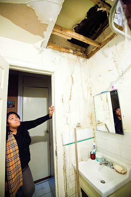 March 7 - Raysette Mercedes, looks at a leaky hole in her Creston Avenue apartment's bathroom ceiling. Rats and roaches invaded the premises.
