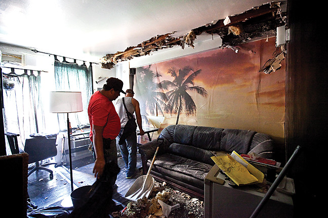 July 10 - Restoration workers, remove debris in Victor Marrero's apartment on the 6th floor of 3840 Orloff Ave. a day after a fire struck the building.
