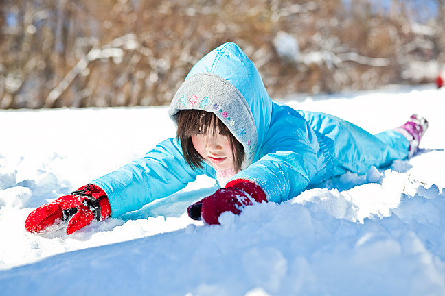 Adela Schwartz, 5, slides on her stomach down a steep slope at Ewen Park.