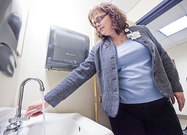 Laura Amerman, Director of Marketing and Philanthropy at Schervier Nursing Care Center turns on a faucet at a 6th floor restroom to show the 'Press' that the water was back on.
