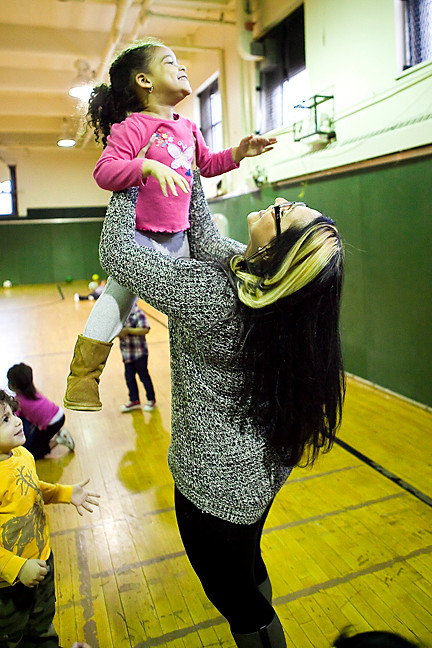 Jayleen Casado, 3, smiles as teacher Reyna Espinal carries her at the Teddy Bears Pre-K Class at KHCC.
