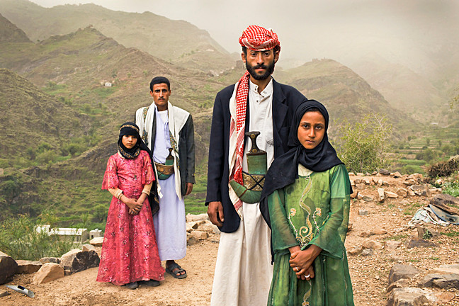 Child brides Tehani, left, and Ghada pose with their husbands outside their home in Hajjah, Yemen.