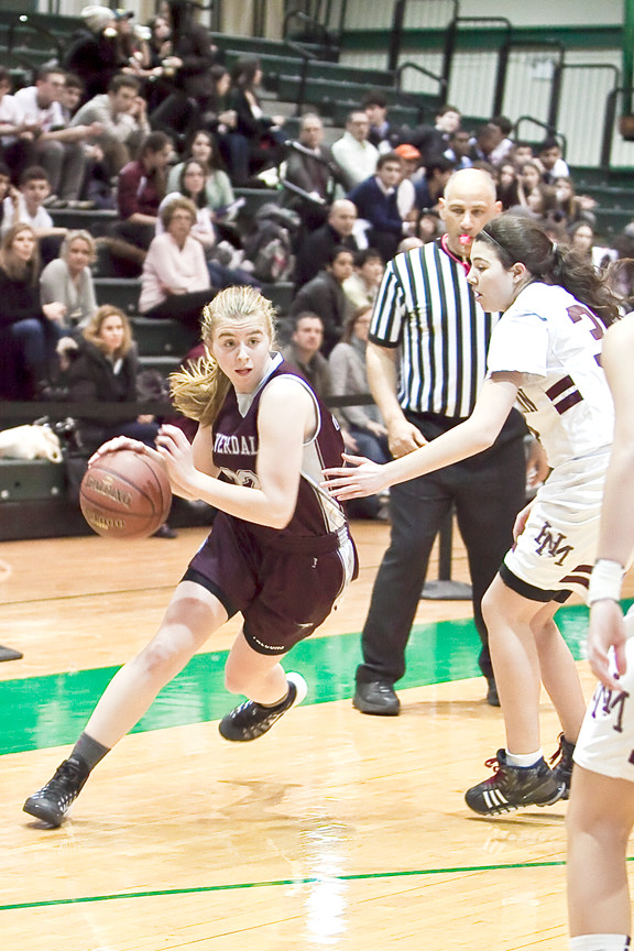 Jennifer Berger, an 11th grader from Riverdale Country School drives the lane past Horace Mann defenders in the women's half of the annual Buzzell Tourney at Manhattan College's Draddy Gym.